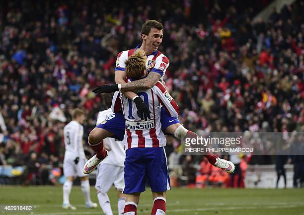 Atletico Madrid's Croatian forward Mario Mandzukic celebrates with teammate after scoring their fourth goal during the Spanish league football match...