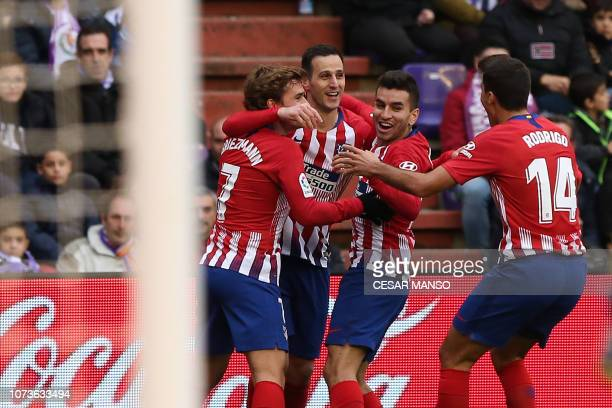 Atletico Madrid's Croatian forward Niko Kalinic celebrates with teammates after scoring a goal during the Spanish League football match between Real...