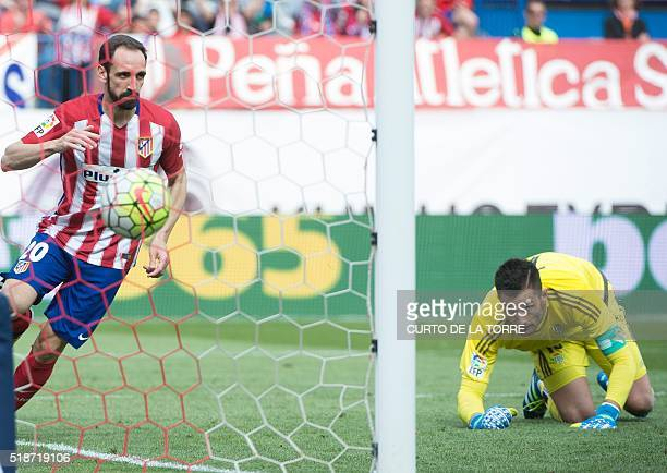 Atletico Madrid's defender Juanfran scores during the Spanish league football match Club Atletico de Madrid vs Real Betis Balompi at the Vicente...