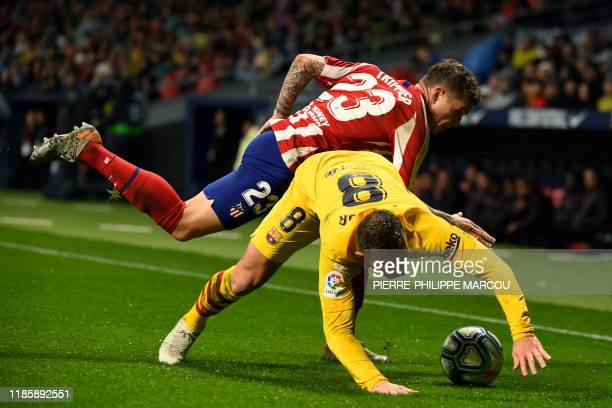 Atletico Madrid's English defender Kieran Trippier challenges Barcelona's Brazilian midfielder Arthur during the Spanish league football match...