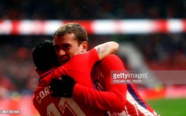 Atletico Madrid's forward Correa celebrates with Atletico Madrid's French forward Antoine Griezmann after scoring a goal during the Spanish league...