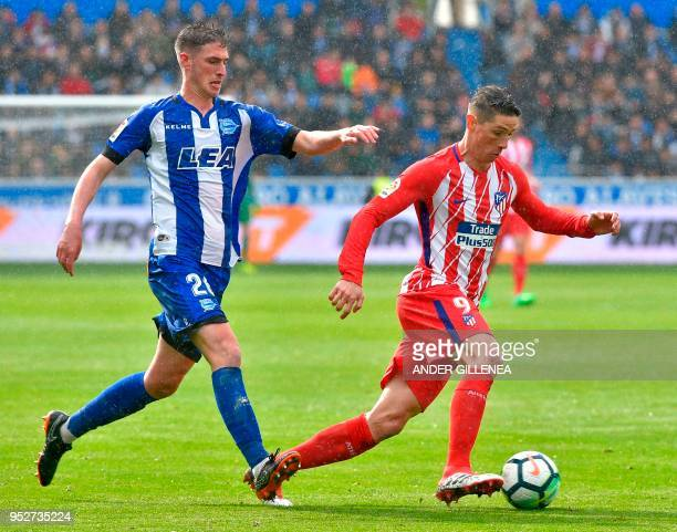 TOPSHOT Atletico Madrid's forward Fernando Torres challenges Alaves' Spanish defender Adrian Dieguez during the Spanish league football match...