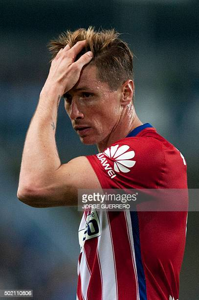 Atletico Madrid's forward Fernando Torres touches his head during the Spanish league football match Malaga CF vs Club Atletico de Madrid at La...