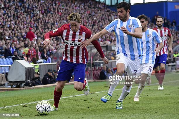 Atletico Madrid's forward Fernando Torres vies with Malaga's defender Miguel Torres during the Spanish league football match Club Atletico de Madrid...
