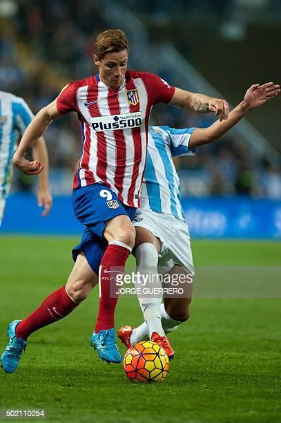 Atletico Madrid's forward Fernando Torres vies with Malaga's midfielder Jose Luis Garcia Recio during the Spanish league football match Malaga CF vs...