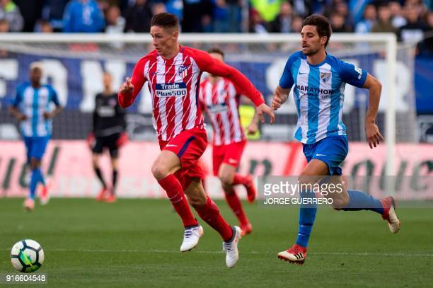Atletico Madrid's forward Fernando Torres vies with Malaga's midfielder Adrian Gonzalez during the Spanish league football match between Malaga CF...