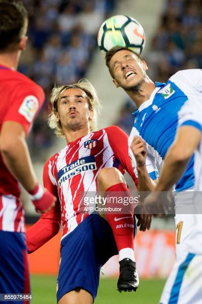 Atletico Madrid's forward from France Antoine Griezmann vies with Leganes' Argentinian midfielder Alexander Szymanowski during the Spanish league...