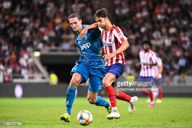 Atletico Madrid's forward Joao Felix vies with Juventus' midfielder Adrien Rabiot during the International Champions Cup football match between...