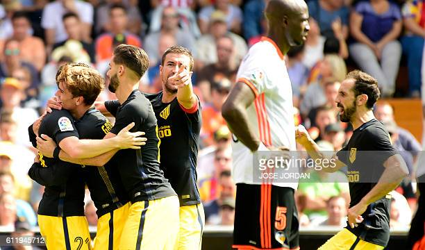 Atletico Madrid's French forward Antoine Griezmann celebrates a goal with teammates during the Spanish league football match Valencia FC vs Club...