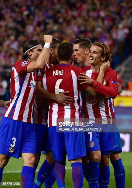 Atletico Madrid's French forward Antoine Griezmann celebrates a penalty goal with teammates during the UEFA Champions League quarter final first leg...