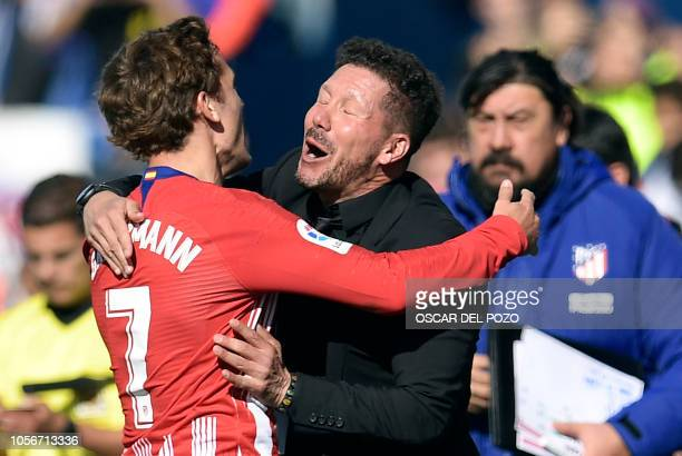 Atletico Madrid's French forward Antoine Griezmann celebrates after scoring the opening goal with Atletico Madrid's Argentinian coach Diego Simeone...
