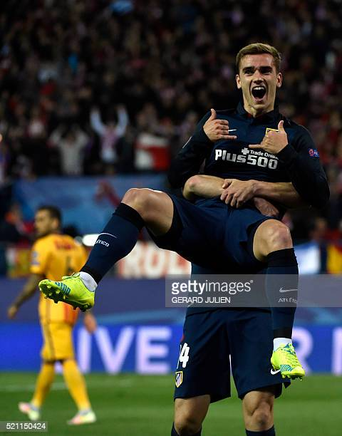 Atletico Madrid's French forward Antoine Griezmann celebrates after scoring with Atletico Madrid's midfielder Gabi during the Champions League...