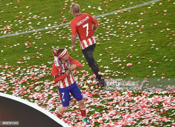 Atletico Madrid's French forward Antoine Griezmann celebrates their victory past his father Alain Griezmann after winning the UEFA Europa League...