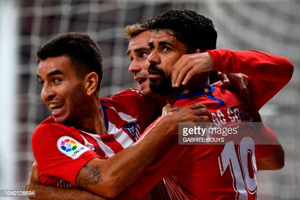 Atletico Madrid's French forward Antoine Griezmann celebrates with Atletico Madrid's Argentinian forward Angel Correa and Atletico Madrid's Spanish...
