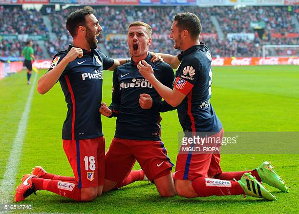 Atletico Madrid's French forward Antoine Griezmann celebrates with teammates defender Jesus Gamez and midfielder Koke after scoring a goal during the...