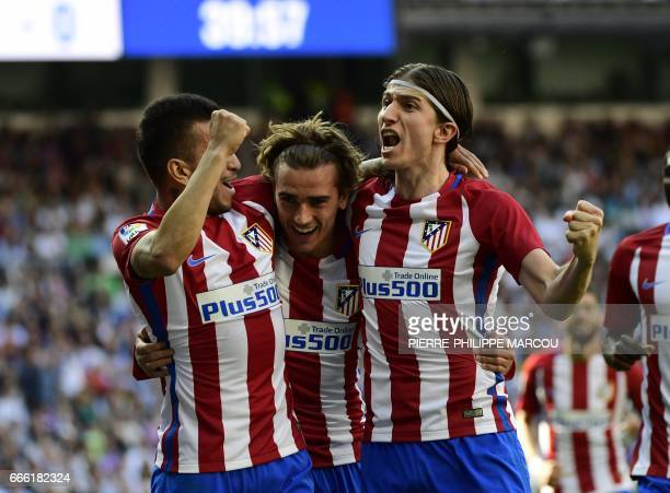 Atletico Madrid's French forward Antoine Griezmann celebrates with Atletico Madrid's Argentinian midfielder Angel Correa and Atletico Madrid's...