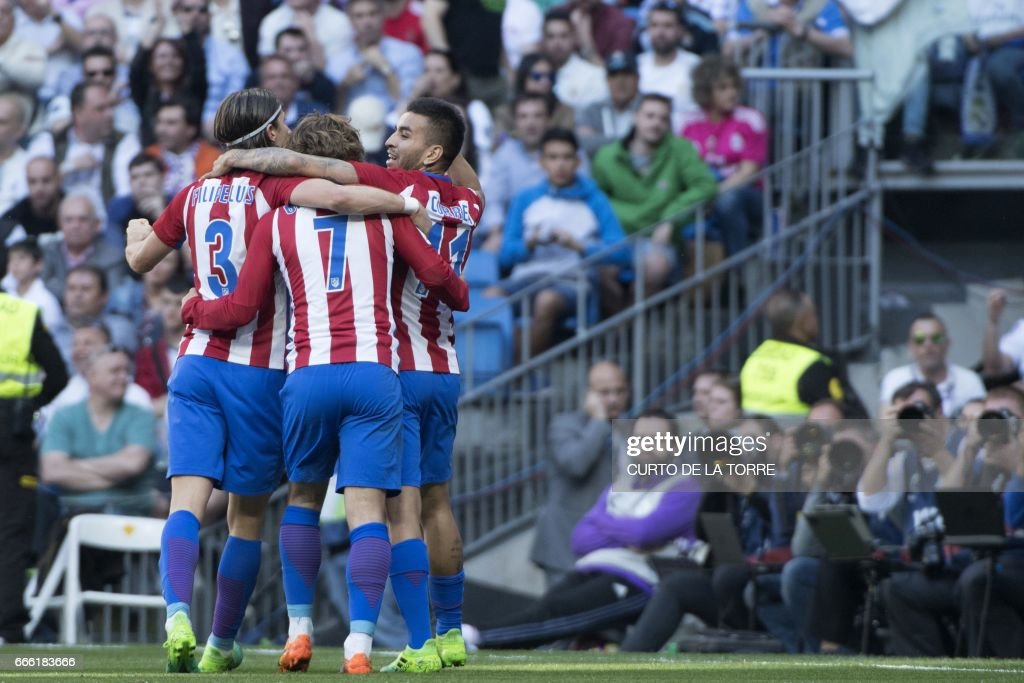 Atletico Madrid's French forward Antoine Griezmann (C) celebrates with Atletico Madrid's Argentinian midfielder Angel Correa (R) and Atletico Madrid's Brazilian defender Filipe Luis (L) after scoring a goal during the Spanish league football match Real Madrid CF vs Club Atletico de Madrid at the Santiago Bernabeu stadium in Madrid on April, 8, 2017. /