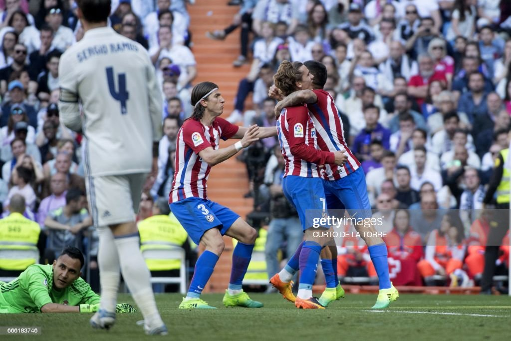 Atletico Madrid's French forward Antoine Griezmann (2L) celebrates with Atletico Madrid's Argentinian midfielder Angel Correa (R) and Atletico Madrid's Brazilian defender Filipe Luis (C) after scoring a goal during the Spanish league football match Real Madrid CF vs Club Atletico de Madrid at the Santiago Bernabeu stadium in Madrid on April, 8, 2017. /