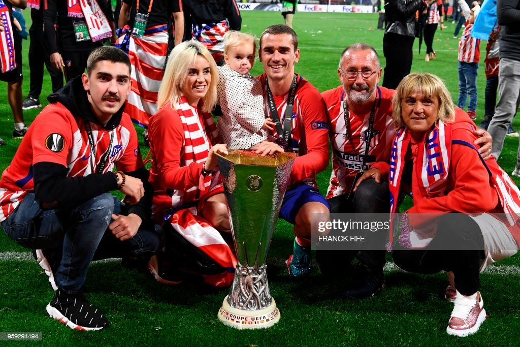 TOPSHOT - Atletico Madrid's French forward Antoine Griezmann (C) celebrates with the trophy with his family, (from L-R) his brother Théo Griezemann, his wife Erika Choperana, his daughter Mia Griezmann, his father Alain Griezmann and his mother Isabelle Lopes, after the UEFA Europa League final football match between Olympique de Marseille and Club Atletico de Madrid at the Parc OL stadium in Decines-Charpieu, near Lyon on May 16, 2018. (Photo by FRANCK FIFE / AFP) / The erroneous mention[s] appearing in the metadata of this photo by FRANCK FIFE has been modified in AFP systems in the following manner: [Atletico Madrid's French forward Antoine Griezmann] instead of [Atletico Madrid's Spanish forward Fernando Torres]. Please immediately remove the erroneous mention[s] from all your online services and delete it (them) from your servers. If you have been authorized by AFP to distribute it (them) to third parties, please ensure that the same actions are carried out by them. Failure to promptly comply with these instructions will entail liability on your part for any continued or post notification usage. Therefore we thank you very much for all your attention and prompt action. We are sorry for the inconvenience this notification may cause and remain at your disposal for any further information you may require.