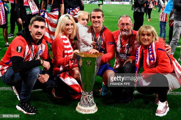 TOPSHOT Atletico Madrid's French forward Antoine Griezmann celebrates with the trophy with his family his brother Théo Griezemann his wife Erika...