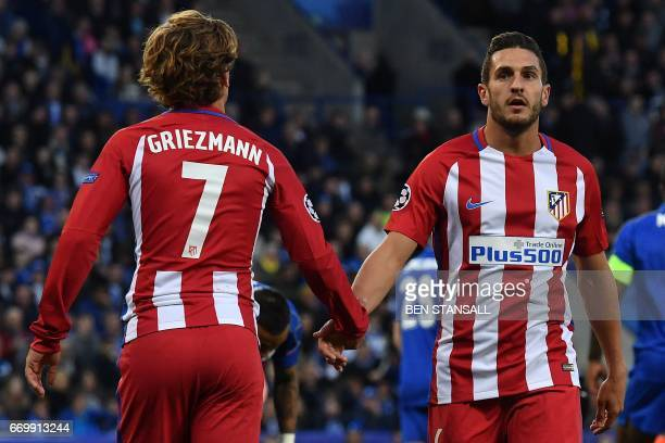 Atletico Madrid's French forward Antoine Griezmann congratulates Atletico Madrid's Spanish midfielder Koke during the UEFA Champions League...