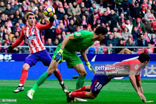 Atletico Madrid's French forward Antoine Griezmann eyes the ball before scoring past Girona's Moroccan goalkeeper Yassine Bounou next to Atletico...