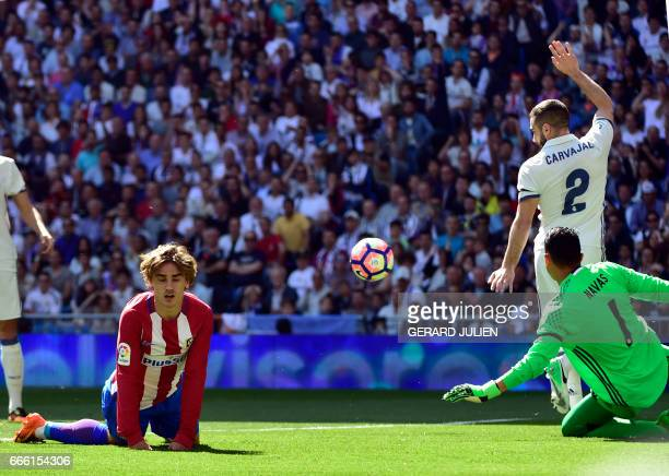 Atletico Madrid's French forward Antoine Griezmann falls on the pitch beside Real Madrid's defender Dani Carvajal and Real Madrid's Costa Rican...
