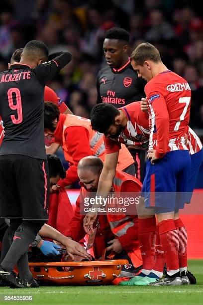 Atletico Madrid's French forward Antoine Griezmann looks at Arsenal's French defender Laurent Koscielny before being removed on a stretcher during...