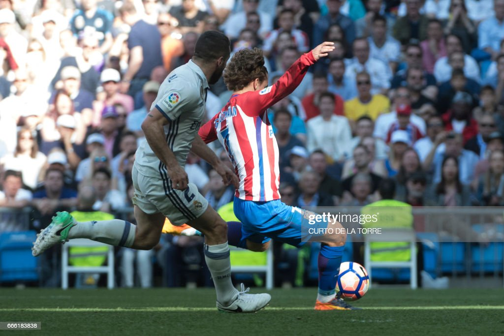 Atletico Madrid's French forward Antoine Griezmann (R) scores a goal during the Spanish league football match Real Madrid CF vs Club Atletico de Madrid at the Santiago Bernabeu stadium in Madrid on April, 8, 2017. /