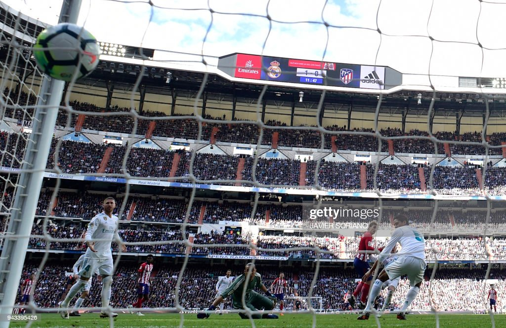 Atletico Madrid's French forward Antoine Griezmann (2R) scores a goal during the Spanish league football match between Real Madrid CF and Club Atletico de Madrid at the Santiago Bernabeu stadium in Madrid on April 8, 2018. /