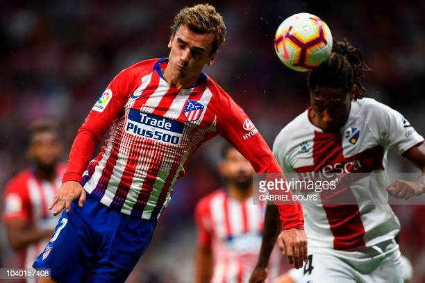Atletico Madrid's French forward Antoine Griezmann vies for the ball with SD Huesca's Portuguese defender Ruben Semedo during the Spanish league...
