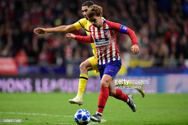 Atletico Madrid's French forward Antoine Griezmann vies with Borussia Dortmund's Moroccan defender Achraf Hakimi prior to scoring a goal during the...