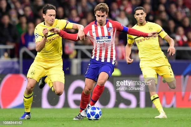TOPSHOT Atletico Madrid's French forward Antoine Griezmann vies with Borussia Dortmund's Danish midfielder Thomas Delaney and Borussia Dortmund's...