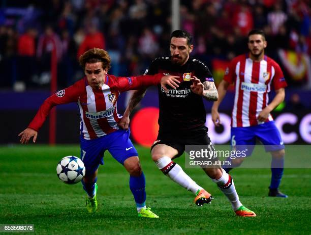 Atletico Madrid's French forward Antoine Griezmann vies with Leverkusen's defender Roberto Hilbert during the UEFA Champions League round of 16...
