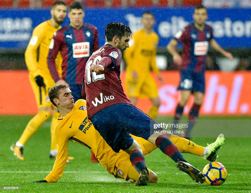 Atletico Madrid's French forward Antoine Griezmann (L) vies with Eibar's Portuguese defender Paulo Oliveira during the Spanish league football match between SD Eibar and Club Atletico de Madrid at the Ipurua stadium in Eibar on January 13, 2018. /