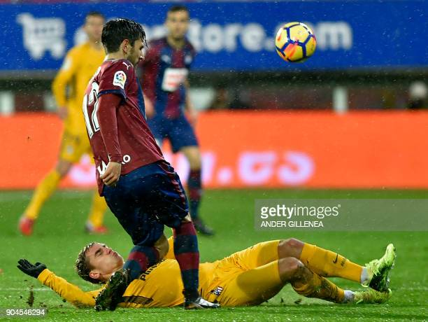Atletico Madrid's French forward Antoine Griezmann vies with Eibar's Portuguese defender Paulo Oliveira during the Spanish league football match...