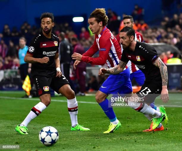 Atletico Madrid's French forward Antoine Griezmann vies with Leverkusen's midfielder Karim Bellarabi and Leverkusen's defender Roberto Hilbert during...