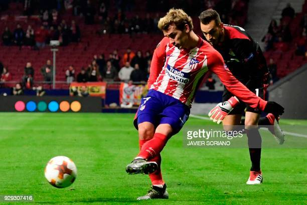 Atletico Madrid's French forward Antoine Griezmann vies with Lokomotiv Moscow's Russian goalkeeper Guilherme during the Europa League Round of 16...