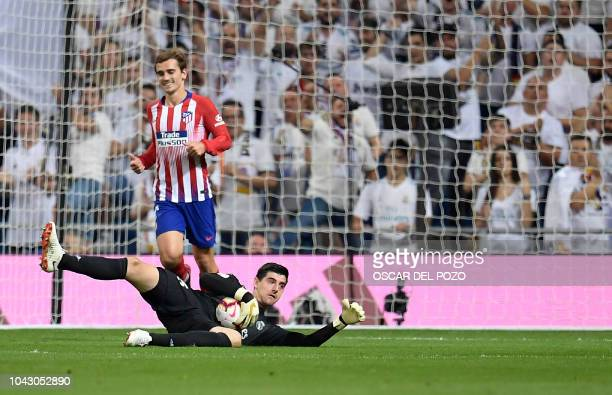Atletico Madrid's French forward Antoine Griezmann vies with Real Madrid's Belgian goalkeeper Thibaut Courtois during the Spanish league football...