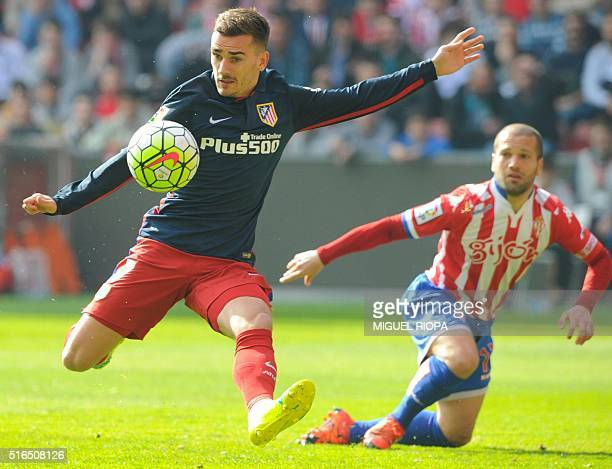 Atletico Madrid's French forward Antoine Griezmann vies with Sporting Gijon's defender Alberto Lora during the Spanish league football match Real...