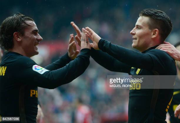 Atletico Madrid's French forward Kevin Gameiro celebrates with teammates after scoring a goal during the Spanish league football match Real Sporting...