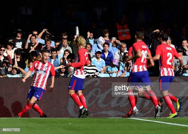 Atletico Madrid's French forward Kevin Gameiro celebrates with teammates after scoring a goal during the Spanish league football match RC Celta de...