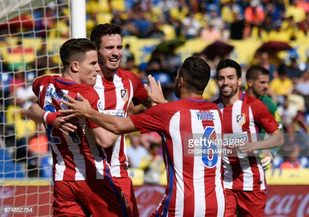 Atletico Madrid's French forward Kevin Gameiro celebrates with Atletico Madrid's midfielder Saul Niguez and teammates after scoring during the...
