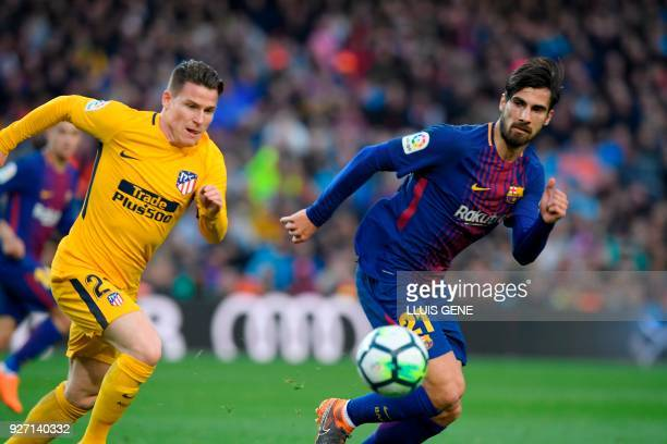 Atletico Madrid's French forward Kevin Gameiro vies with Barcelona's Portuguese midfielder Andre Gomes during the Spanish league football match FC...