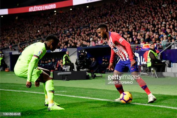 Atletico Madrid's French midfielder Thomas Lemar challenges Barcelona's Portuguese defender Nelson Semedo during the Spanish league football match...