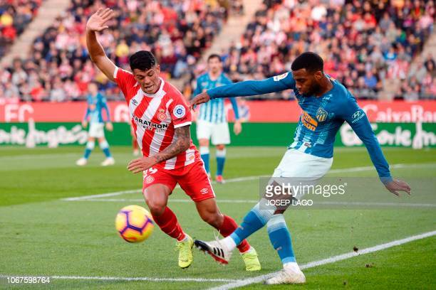 Atletico Madrid's French midfielder Thomas Lemar challenges Girona's Spanish midfielder Pedro Porro during the Spanish league football match between...