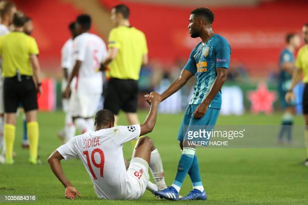 Atletico Madrid's French midfielder Thomas Lemar helps Monaco's French defender Djibril Sidibe to stand up at the end of the UEFA Champions League...