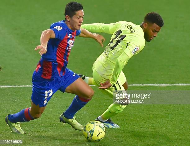 Atletico Madrid's French midfielder Thomas Lemar vies with Eibar's Japanese forward Yoshinori Muto during the Spanish league football match SD Eibar...