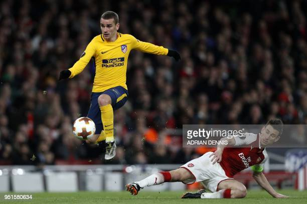 Atletico Madrid's French striker Antoine Griezmann evades a tackle by Arsenal's French defender Laurent Koscielny on his way to scoring their first...