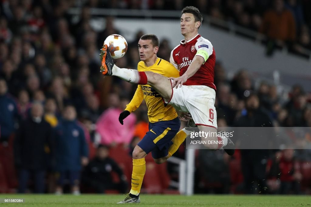 Atletico Madrid's French striker Antoine Griezmann (L) vies with Arsenal's French defender Laurent Koscielny on his way to scoring their first goal during the UEFA Europa League first leg semi-final football match between Arsenal and Atletico Madrid at the Emirates Stadium in London on April 26, 2018. - The game finished 1-1.